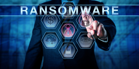 executable: Male cybersecurity threat systems manager pushing RANSOMWARE on a transparent control interface. Computer crime concept for a hacking attack restricting file access to seek a ransom from a user. Stock Photo