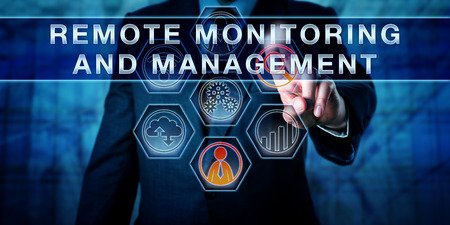 Male corporate business administrator in blue is pushing REMOTE MONITORING AND MANAGEMENT on an interactive control screen. Remote administration software concept. Industry term abbreviated as RMM. Banque d'images