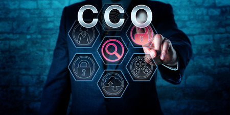 Torso of a male corporate executive touching CCO on an interactive virtual control screen monitor. Business and IT concept for Chief Compliance Officer, regulatory compliance issues and governance.