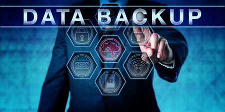 data loss: Business manager pushing DATA BACKUP on an interactive virtual control screen interface. Information technology concept for copying files or databases for future use in data recovery upon data loss.
