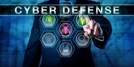 Close up of torso of a man in blue suit raising his left hand to touch the phrase CYBER DEFENSE. A closed padlock and cloud computing icon do light up in green. Hacker symbol is highlighted purple.