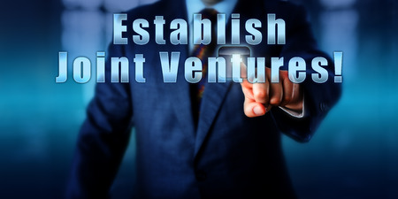 establish: Corporate executive is touching Establish Joint Ventures! on an interactive control monitor. Business growth strategy concept, motivational metaphor and call to action. Torso shot without head. Stock Photo