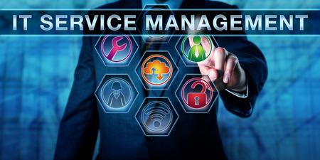 Business manager è a contatto con la gestione dei servizi su uno schermo interattivo virtuale. Informazioni concetto di tecnologia per ITSM e metafora di affari. Diverse icone degli strumenti si illuminano di colore. Chiudere il tiro. Archivio Fotografico - 61131086