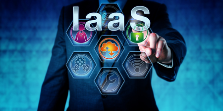 to maintain: Manager is pressing IaaS on an interactive touch screen. Information technology concept for cloud computing and acronym for Infrastructure as a Service. Close up shot of business man in blue suit.