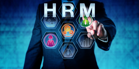ongoing: Human resources manager is pressing HRM on an interactive touch screen monitor. Business metaphor and acronym for Human Resource Management. Concept for work force planning.