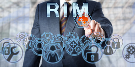 technology metaphor: Business manager is pressing RIM onscreen. Computer networking and information technology metaphor. Business IT services concept and acronym for Remote Infrastructure Management. Stock Photo