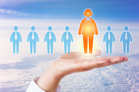 The only one female candidate in an otherwise all male lineup of white collar professionals is standing out in an open palm of hand high above a dense cloudscape on a sunny morning. Business concept. Stock Photo