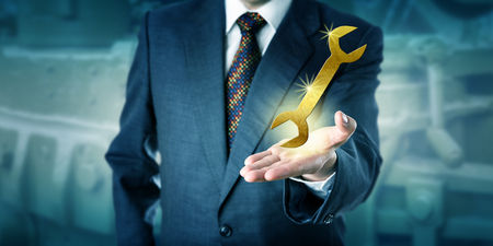 Unrecognizable male white collar professional is presenting a sparkling golden virtual wrench in the palm of his left hand. Business concept for solution, support, success, capability and innovation.