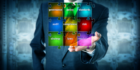 Male GRC management professional presenting a virtual planning matrix in form of a jigsaw puzzle in his left palm of hand. Business concept for corporate governance, risk management and compliance.