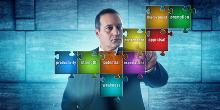 appraisal: HR manager with focused look touching a jigsaw puzzle imprinted with performance appraisal terms. Concept for career development, self assessment, human resources management and talent acquisition. Stock Photo