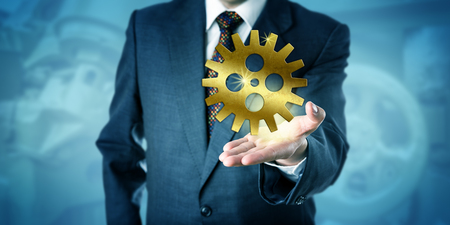 cog wheel: Businessman is showing one single golden cog wheel in the open palm of his left hand. Business concept for services solution, entrepreneurial inspiration and mechanical engineering success. Stock Photo