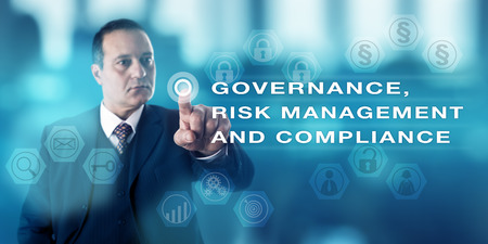 gobierno corporativo: Mature business man with focused gaze is pushing a virtual button to activate GOVERNANCE, RISK MANAGEMENT AND COMPLIANCE onscreen. Business concept for corporate governance, laws and regulations. Foto de archivo