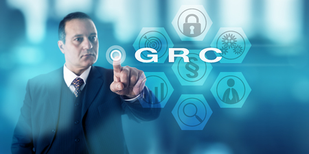 Experienced corporate governance officer is activating GRC onscreen. Business concept and information security metaphor for Governance, Risk Management and Compliance procedures and processes. Stock Photo