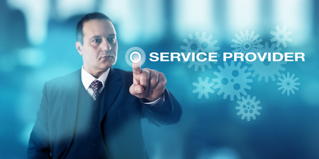 technology metaphor: Businessman with serious look is pushing a virtual button highlighting the words SERVICE PROVIDER. Business concept and information technology metaphor for any third party or outsourced supplier. Stock Photo