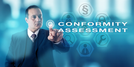 Seasoned male corporate manager pressing CONFORMITY ASSESSMENT via a virtual push button onscreen. Business and technology concept for inspection processes of the observance of technical standards. Stock Photo