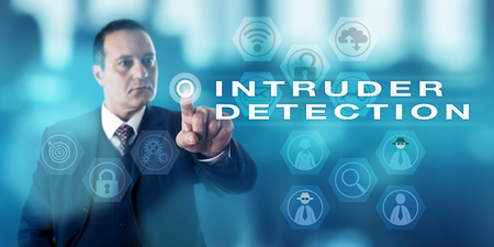 intruder: Experienced male information security director is pushing a virtual button to activate the term INTRUDER DETECTION onscreen. Computer security procedure metaphor and business concept.