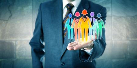 White Collar Manager ein Arbeitsteam von fünf bunten Arbeiter Symbole in der offenen Handfläche der linken Hand zu präsentieren. Business-Konzept für Teambildung, Vielfalt Einbeziehung Kultur und Personallösungen. Standard-Bild