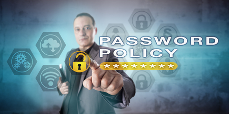administrador de empresas: Mature business administrator highlighting PASSWORD POLICY onscreen. Computer security metaphor and information technology concept for compliance with password authentication rules and regulations.
