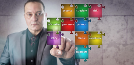 business puzzle: Corporate manager with determined and focused look is touching a piece in a puzzle labeled information. Data management metaphor for information governance, compliance and operational transparency. Stock Photo