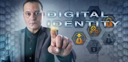 identifiers: Businessman in gray suit with intent look touching DIGITAL IDENTITY onscreen. Business metaphor and information technology concept for identity management, digital identifiers and authentication. Stock Photo