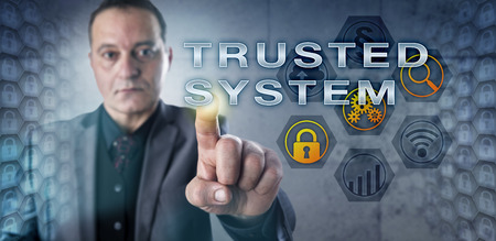 technology metaphor: Experienced male security expert is touching TRUSTED SYSTEM on a virtual monitor. Information technology metaphor and security engineering concept for a system capable of enforcing a security policy. Stock Photo