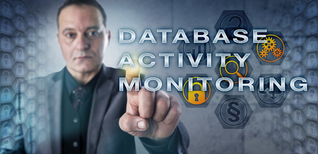 administer: Mature male enterprise data manager is touching DATABASE ACTIVITY MONITORING onscreen. Database security metaphor and information technology concept for continuous database analyzing.