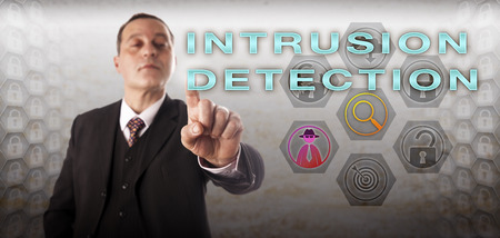 Mature business manager with perky and confident look is activating INTRUSION DETECTION onscreen. Information technology and cybersecurity concept for identifying and monitoring network violations. Stock Photo