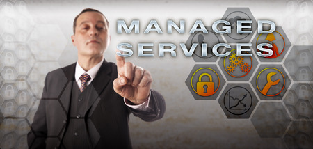 managed: Manager with assertive and perky look is activating MANAGED SERVICES onscreen. Business concept and information technology metaphor for outside handling of IT via automated professional services.