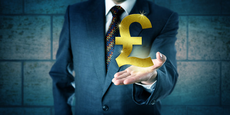 interbank: Forex trader holding a golden British Pound Sterling symbol in the open palm of his left hand. Business concept and financial services metaphor for interbank market, currency, wealth and achievement.