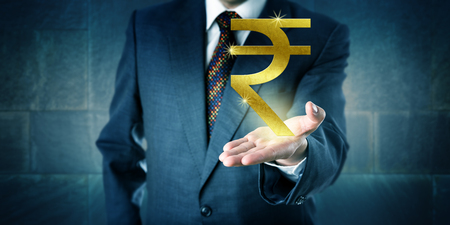 interbank: Businessman offering a golden Indian rupee symbol in the open upward facing palm of his left hand. Business metaphor and financial concept for national currency, interbank market and investment.