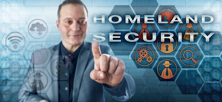 law suit: Happy male agent in business suit with toothless smile is activating HOMELAND SECURITY on an interactive control screen. Law enforcement metaphor and security industry concept for homeland defense.