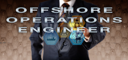 onsite: Businessman in blue suit is pressing OFFSHORE OPERATIONS ENGINEER on an interactive virtual computer monitor. Oil and gas industry career metaphor for an engineering role coordinating project work. Stock Photo