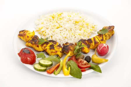 Grilled, marinated morsels of chicken without bones arranged on a plain white plate. Fusion food concept. Called chelo joojeh or jujeh kebab in Persian cuisine. Closeup studio shot on white tabletop.