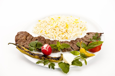 Crispy grilled lamb kebab dish with rice on a plain plate over white table top. Barbecued lean lamb fillet pieces taken off the skewer. Traditional Persian meal. High angle view studio shot. Closeup.