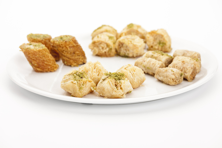 Four pieces of Bokaj cashew baklava presented with assorted oriental sweet pastries on a white plate. Flower shaped lightly baked fillo pastry decorated with fresh ground pistachio nut. Closeup. Stock Photo