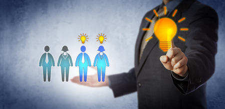 Unrecognizable corporate manager activating training for two employees in a group of four. Business concept for continued professional development, onboarding, and competing for the best talent. Stock Photo