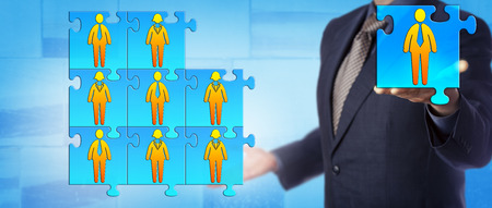 Unrecognizable male business director is offering the final piece to complete his work team puzzle. Human resources concept for team building, collaboration, cooperation and succession planning.