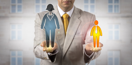 Unrecognizable recruitment consultant comparing a small male worker icon with a huge female employee symbol. HR concept for power relations at the workplace, rivalry, challenge, pay gap, favoritism. Stock Photo