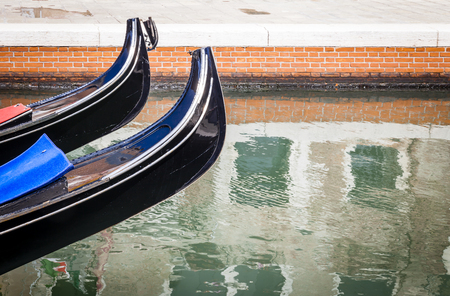 Two prows of Venetian wooden gondola rowing boats rising above rippled sea waters of a side canal in the ancient town of Venice in Italy. Copy space over house reflections distorted by waves. 스톡 콘텐츠