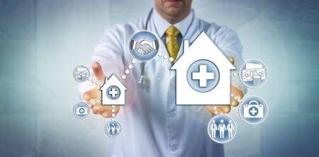 Médico irreconocible que presenta un trato entre un hospital pequeño y una organización de proveedores de atención médica más grande. Concepto de fusiones y adquisiciones sanitarias, economía de escala, consolidación. Foto de archivo