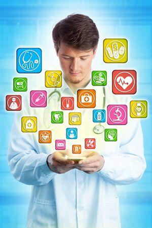 Giovane medico che digita con entrambi i pollici sul suo smartphone mentre naviga tra le app di assistenza sanitaria. Concetto tecnologico per interfaccia utente sanitaria, telemedicina, consultazione remota, accesso mobile.