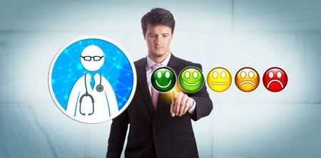 Young smiling business manager is giving a very good rating to a general practitioner via online app. Healthcare technology concept for customer feedback, technology savvy healthcare consumer. 写真素材