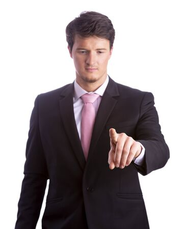 Cut out close-up of confident young businessman pointing index finger at imaginary touch screen, while looking on. Focus is on hand. Studio shot isolated on white background. Business concept. 写真素材