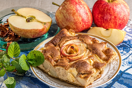 Tasty Apple Pie Piece on a Plate with Apple, Apple slices and mint leaves