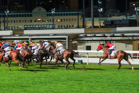 Racehorses ridden by jockeys running fast during the race at race course from start to finish. Striving to victory. Horizontal image, motion blur.