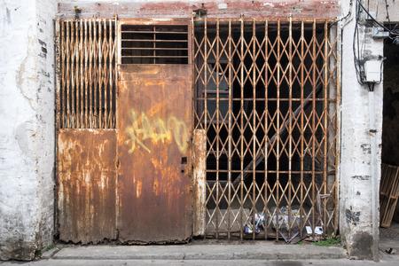 Closed old weathered rusty metal door in slum district.