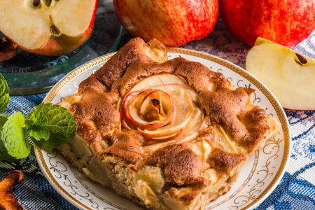 Apple pie cake on plate with fresh red apples. Famous tart with different types of recipes. It is one of a number of American cultural icons. Stock Photo