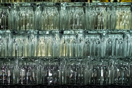 Empty glasses on bar interior background. Artificial lighting creates reflections and glares in glass. Abstract backdrop. Copy space.