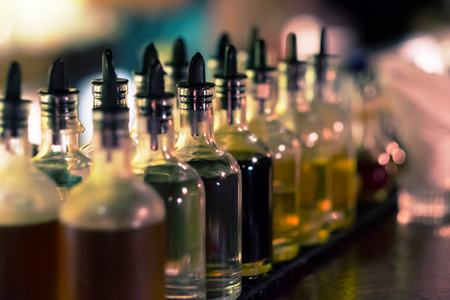 Bottles with syrups for mixing cocktails on bar counter. Alcohol drinks ingredients. Professional cocktail liquors. Horizontal image with selective focus.