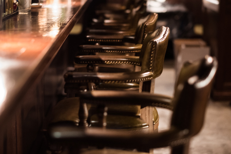 Bar design in classic vintage style. Oak wooden bar counter, comfortable chairs with leather upholstery and cooper rivets. Luxury interior. Great place for relax after work. 스톡 콘텐츠